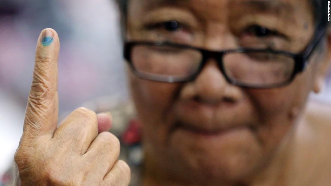 Esteban shows the indelible ink on her finger after casting her vote.