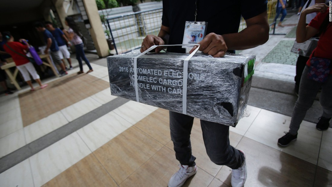 An Election Worker Carries Official Ballots As They Are Distributed To Polling Centers In The Suburban