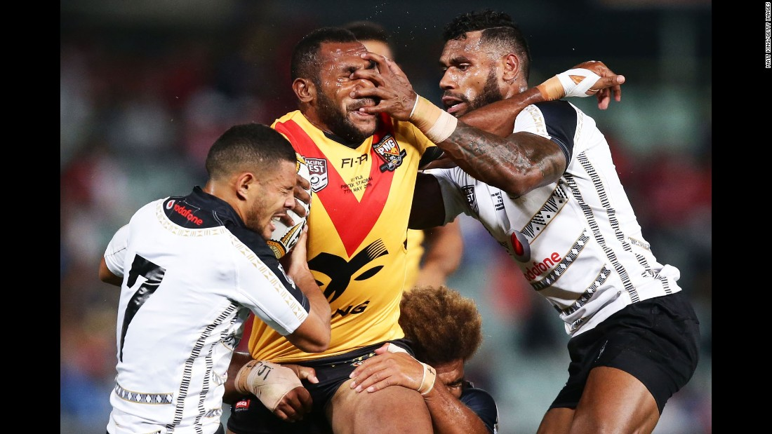 Edward Goma, a rugby player from Papua New Guinea, is tackled by Fiji players during a match in Sydney on Saturday, May 7.