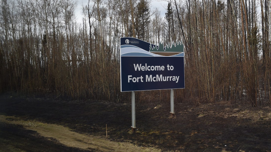 Burned ground surrounds a sign welcoming visitors to Fort McMurray on May 9. The wildfire began Sunday, May 1, and had torched nearly 617,800 acres as of May 10, according to Alberta's Wildfire Management agency. The cause of the blaze was unclear.