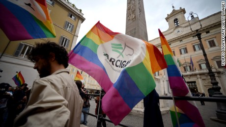 Supporters of same-sex civil unions stand outside the Italian Parliament in Rome on May 11, 2016.