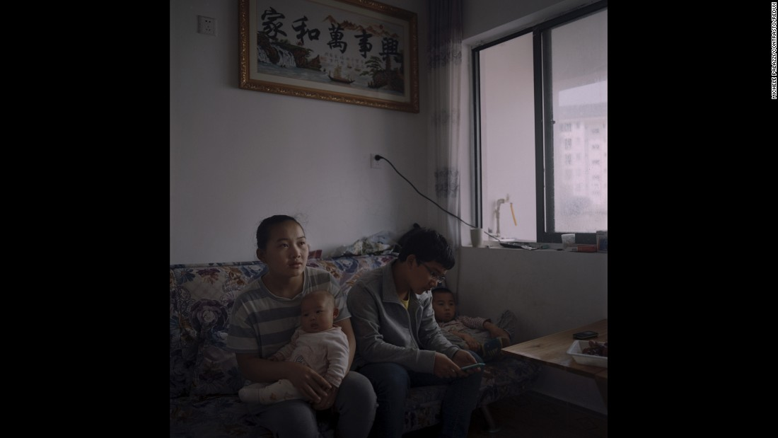 A relocated family watches television in Danzai, China.