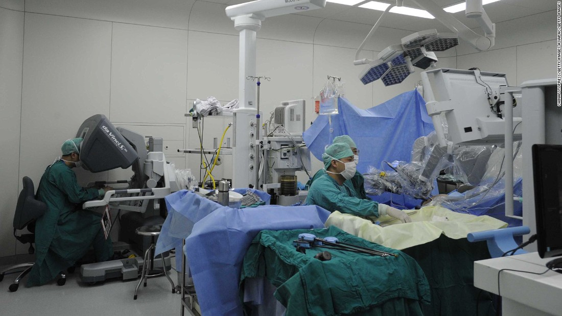 Here the surgeon (left) controls the da Vinci robot  to remove a tumor in a patient. The robot has a magnified 3D vision system which can give the surgeon a clearer view of the operation.