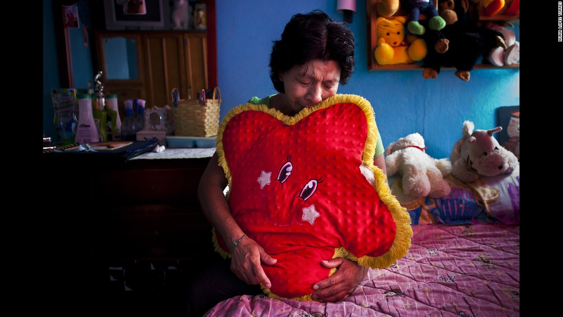 A woman in Mexico City cries in her daughter's bedroom. Her daughter Amairay was an 18-year-old student who disappeared in 2012.