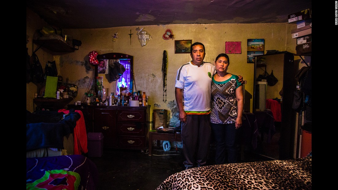 Lorena Ivonne's parents pose for a photo in her room. The 25-year-old disappeared in September when she left the house to go to work. She and her son were living with her parents after a divorce.