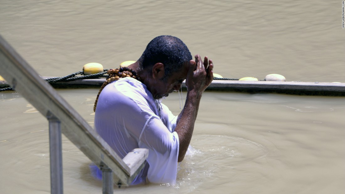 "A pilgrim immerses himself in the waters of the Jordan River. UNESCO recognizes the official site of Jesus' baptism as the east bank of the river in Jordan, called Al-Maghtas (""baptism"")."