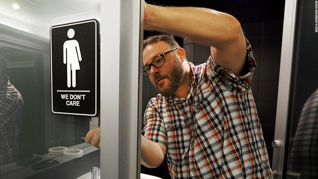 "Manager Jeff Bell applies a gender-neutral sign inside a public restroom at the 21C Museum Hotel in Durham, North Carolina, on Tuesday, May 10. The U.S. Justice Department <a href=""http://www.cnn.com/2016/05/09/politics/north-carolina-hb2-justice-department-deadline/"" target=""_blank"">has filed a civil rights lawsuit</a> over the state's so-called bathroom bill, which bans people from using public bathrooms that do not correspond with their biological sex. Since its passage in March, North Carolina has become a national battleground on the issue of transgender rights."