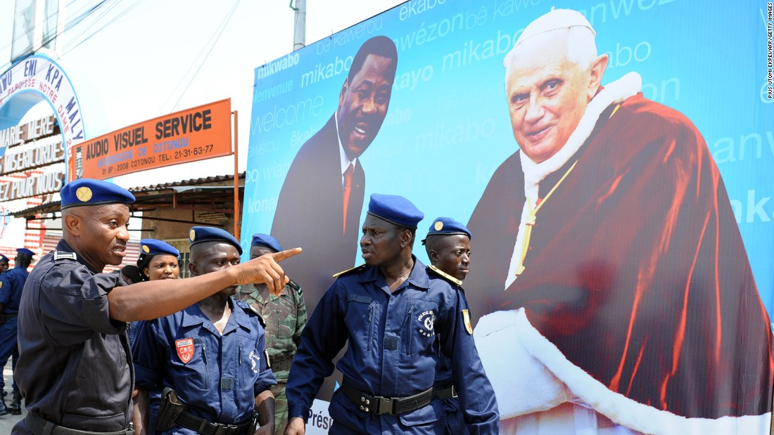 Policemen in Benin walk past a sign announcing a mass conducted by Pope Benedict XVI during his visit in 2011. <br />