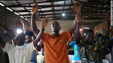 DOLO TOWN, LIBERIA - AUGUST 24:  Church members pray as Rev. James Blamah speaks about the Ebola epidemic during a Sunday service at his church on August 24, 2014 in Dolo Town, Liberia. Members of the Bethlehem World Outreach Ministry International prayed for Liberia's healthcare workers, who have become some of the Ebola epidemic's most frequent casualties. The government issued a quarantine August 20 to stop the Ebola epidemic from spreading from the rural community of some 20,000 people, located near Liberia's international airport, and the military is stopping residents from leaving the area. Local Ministry of Health personnel say they have sent 20 sick people in the previous days to the Doctors Without Borders (MSF), treatment center for to be tested for Ebola.  (Photo by John Moore/Getty Images)