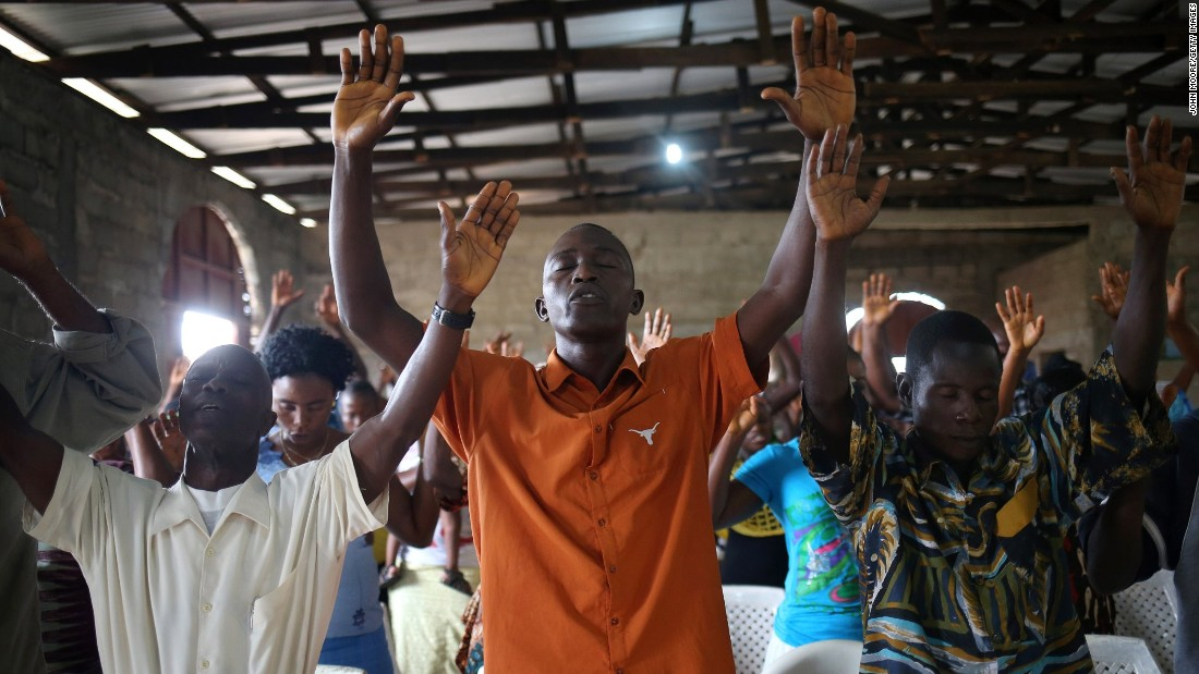 Church members of the Bethlehem World Outreach Ministry International in Liberia pray at a Sunday service during the Ebola epidemic.