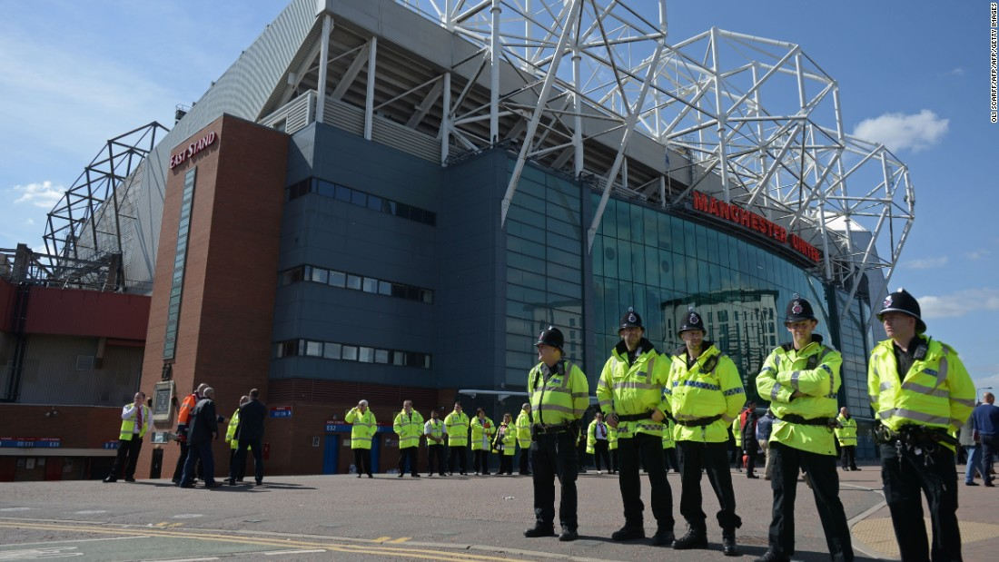 Police officers stand on duty outside Old Trafford stadium after the English Premier League football match between Manchester United and Bournemouth was abandoned Sunday.