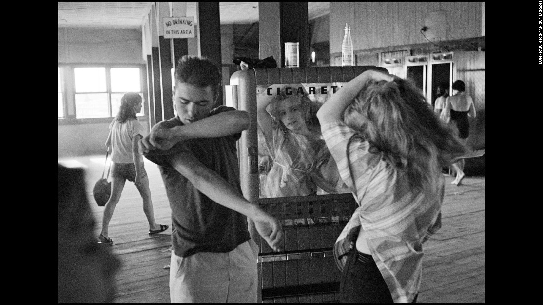 A girl in New York fixes her hair in front of a mirrored cigarette machine in 1959.
