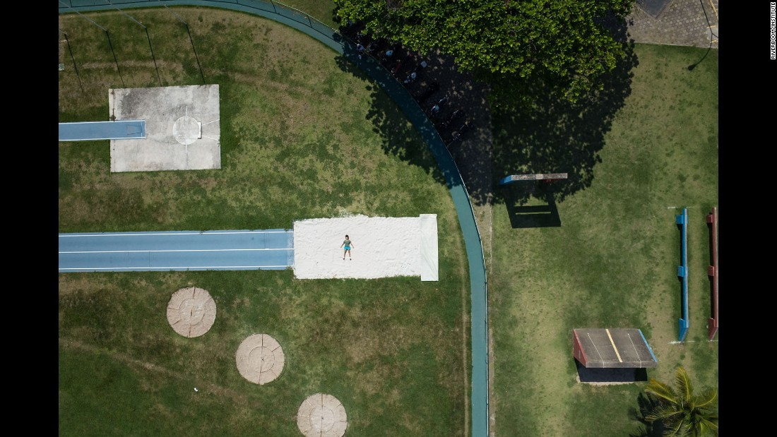 A person poses in a long-jump pit at the Military School of Physical Education.