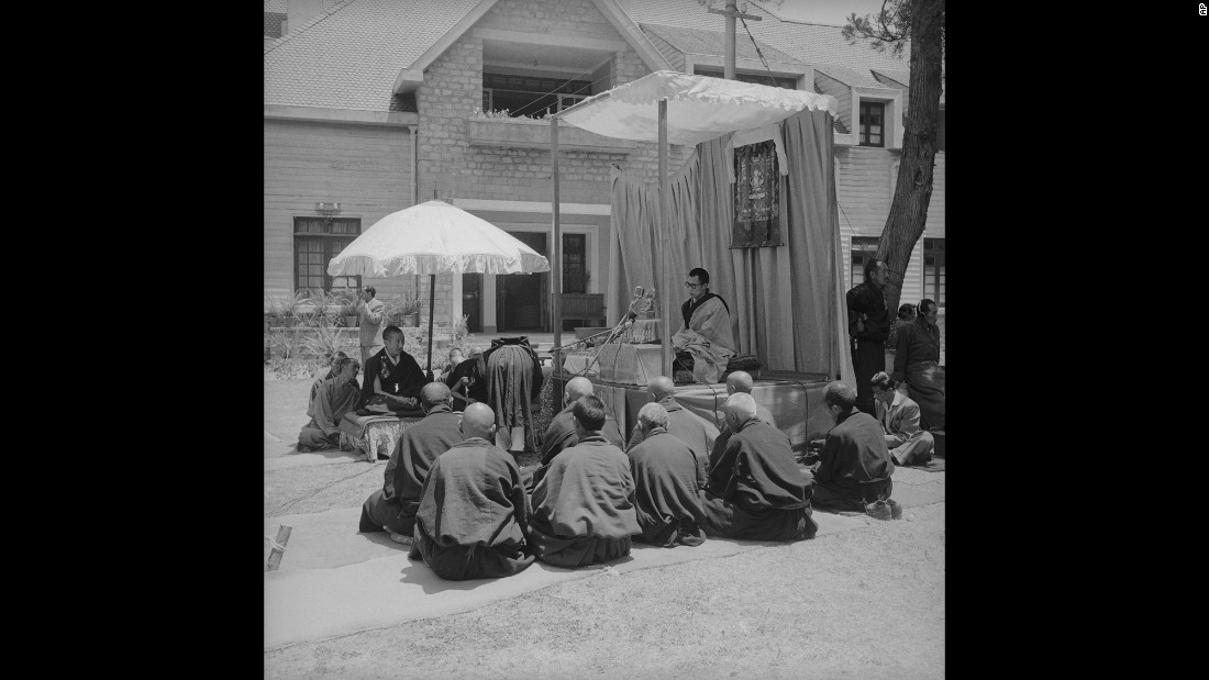 The Dalai Lama sits under a portrait of Buddha as he gives an address at the Birla House. Leading Tibetan monks sit on his left. His tutors sit on his right. During his address, the Dalai Lama expressed hope that the strife in his country was only a passing phase, and he urged the gathering to pray for a return of peace to Tibet.
