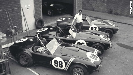 Car designer Carroll Shelby with the three Shelby Cobra roadsters that would win the 1963 USRRC Manufacturer's Championship. The brand worked with David Yurman to produce a black rubber-coated steel chronograph with the Shelby double racing stripe on the dial.
