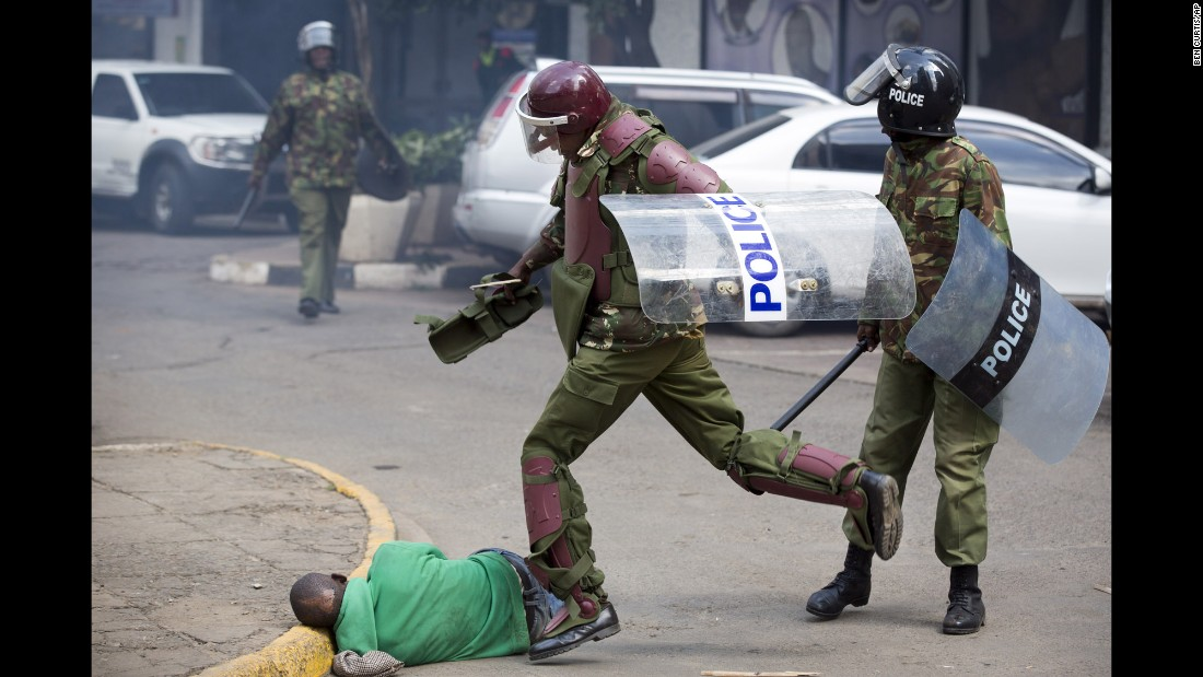 "A Kenyan riot policeman repeatedly kicks a protester as he lies in the street after tripping  while trying to flee from them on Monday, May 16. Ben Curtis, Associated Press' East Africa photographer and acting bureau chief in Nairobi said this man was ""chased across the street and fell down. As he lay motionless on the ground the riot policeman who had pursued him beat him with a stick, breaking it in half, and then continued to kick him half a dozen times, while two other police joined in. Eventually another officer walked up and directed the police to move away, leaving the man lying in the street. ... Later in the afternoon he was located in the Kibera slum of Nairobi -- injured but alive."""