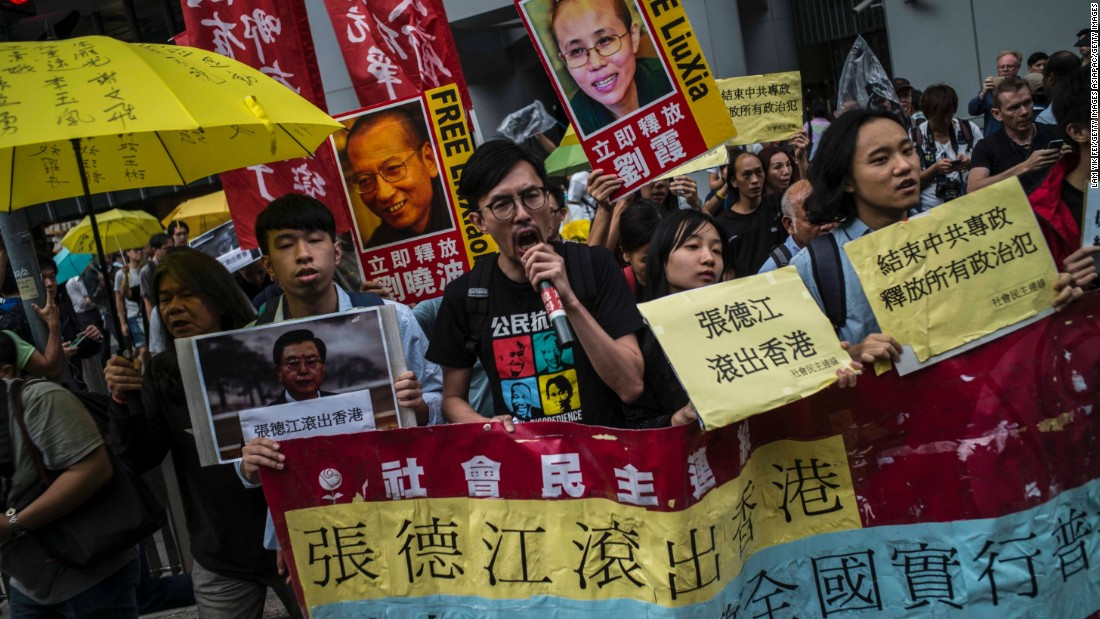 Hong Kong pro-democracy activists hold pictures of Zhang, as well as images of detained Chinese Nobel Peace laureate Liu Xiaobo and his wife Liu Xia, as they march to Government House on May 17.