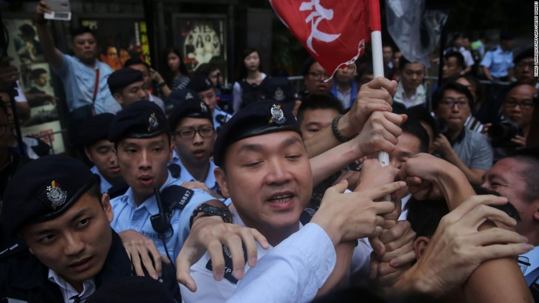 Hong Kong police try to confiscate a flag during a League of Social Democrats protest outside the Central Government Headquarters in Hong Kong, on the first day of Zhang Dejiang's visit, Tuesday, May 17.