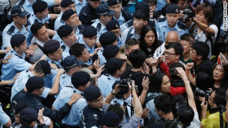 Pro-democracy activists scuffle with police officers on the road to the Government House where the dinner is held for the visiting chairman of the Standing Committee of China's National People's Congress, Zhang Dejiang, in Hong Kong, Tuesday, May 17, 2016. Hong Kong authorities rolled out a massive security operation on Tuesday as they braced for protests during a top Beijing official's visit to the semiautonomous city, where tensions are rising over Chinese rule. (AP Photo/Kin Cheung)
