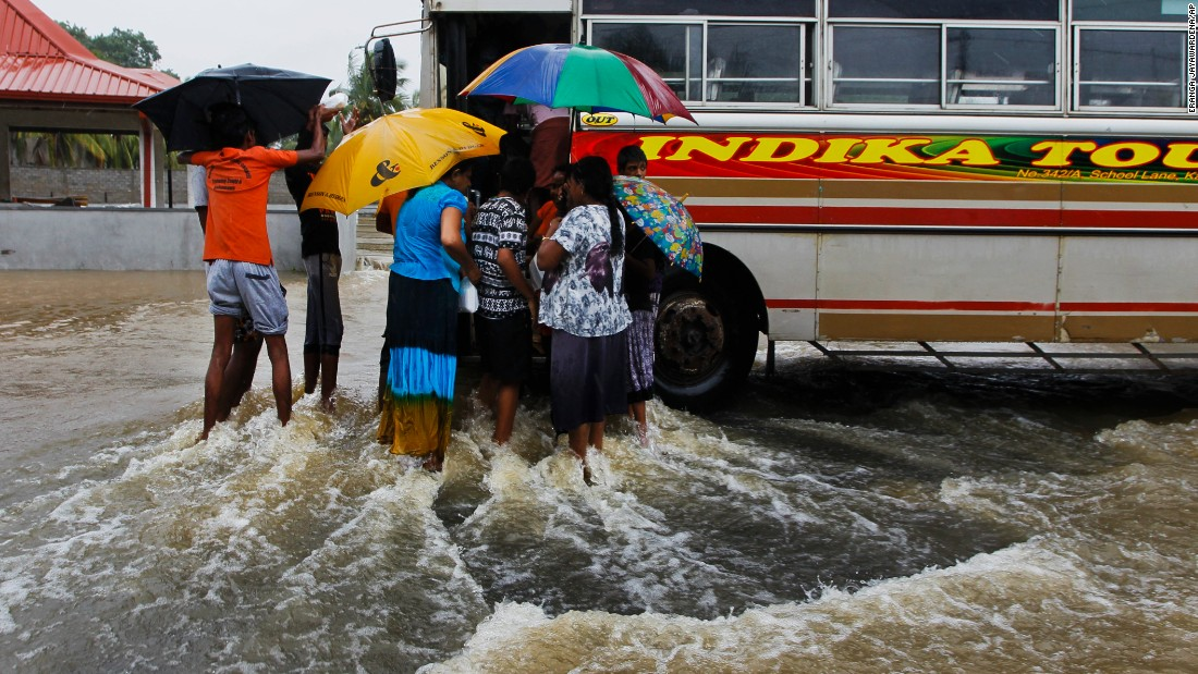 Flood victims flock around a bus to receive food parcels on a inundated road in Colombo on May 17.