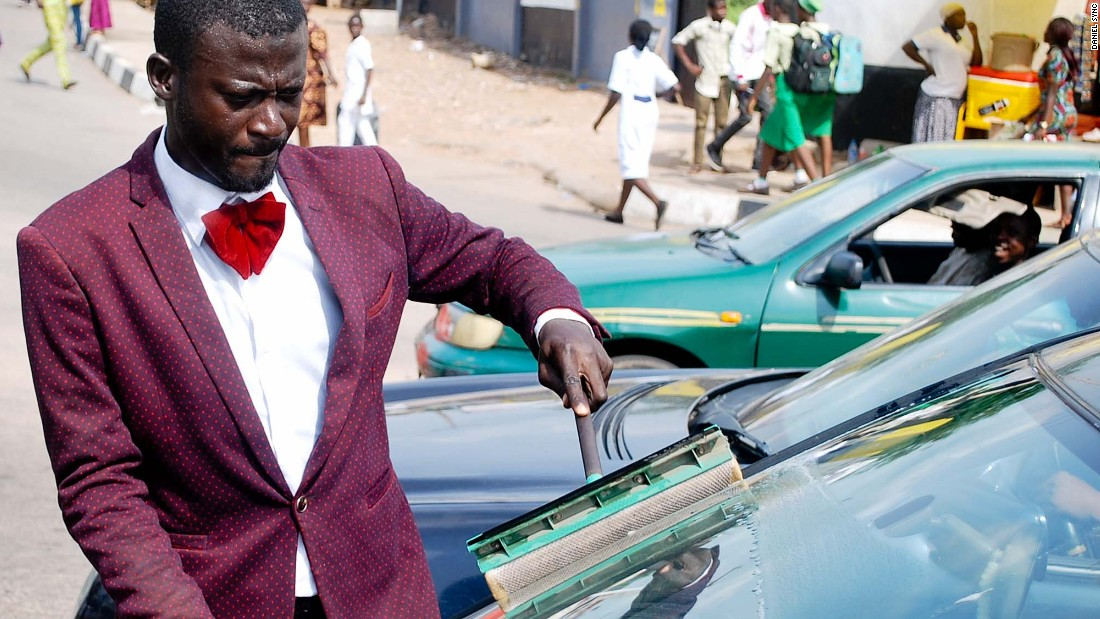 "Abdulahi Olatoyan wears sharp suits while working as a car window washer in Abeokuta, southwest Nigeria. ""I didn't want to be wandering around the streets doing nothing"" he says."
