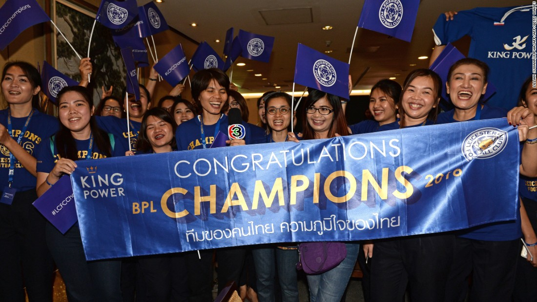 Leicester City's jubilant players and staff are greeted by a banner of congratulations as they arrive in Thailand.