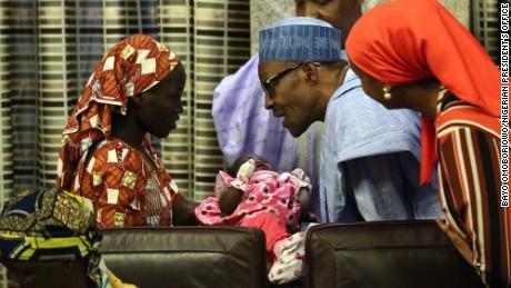 Nigerian President Muhammadu Buhari hold Amina Ali's baby.