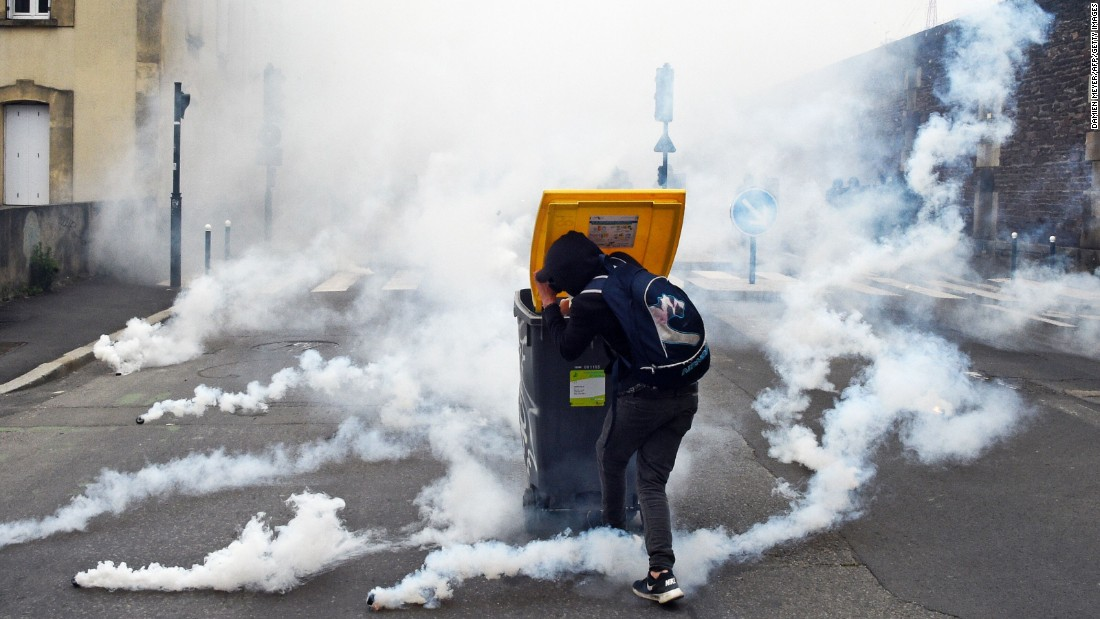 A man in Rennes, France, shields himself from tear gas canisters during a demonstration against the government's planned labor law reforms on Tuesday, May 17.