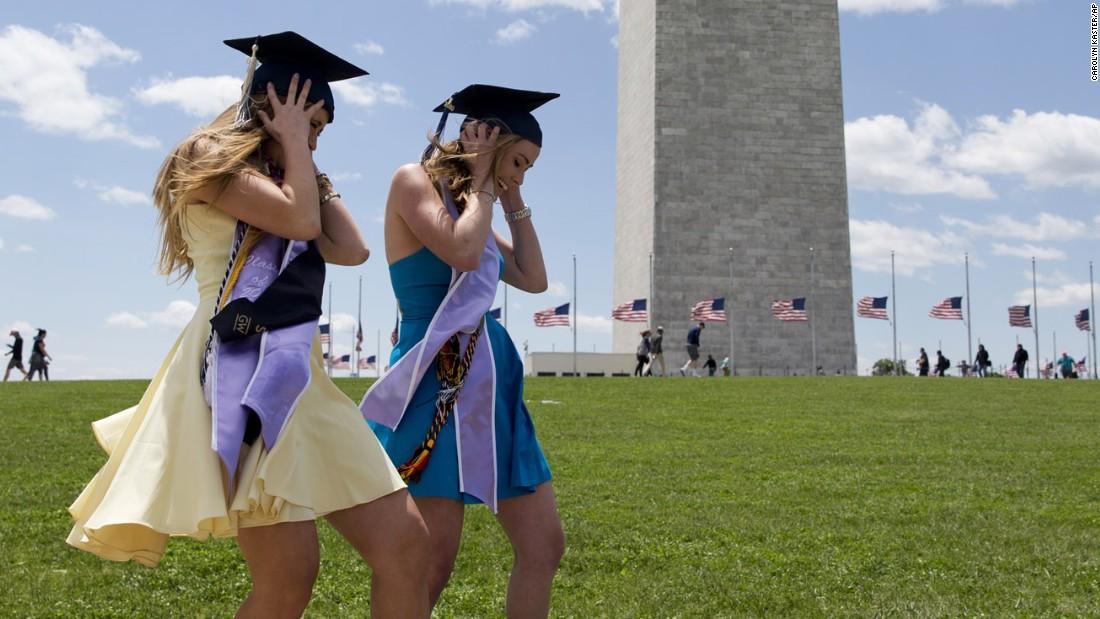 Two graduates of George Washington University struggle against the wind as they pose for photos near the Washington Monument on Sunday, May 15.