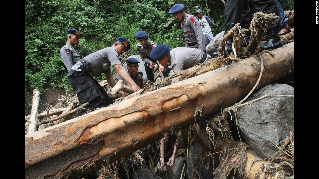 Rescuers recover a body after flooding hit the Dua Warna waterfall in Sibolangit, Indonesia, on Monday, May 16. Nearly two dozen students were missing in rain-triggered floods and landslides at the waterfall.