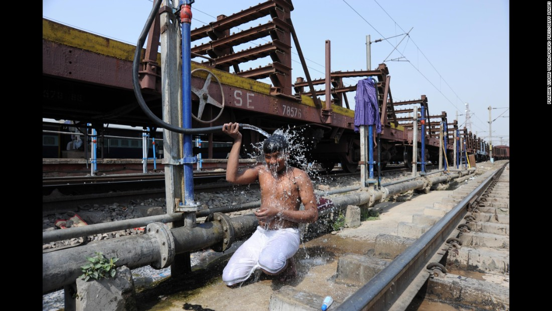 A commuter cools off at a railway junction during a hot day in Allahabad, India, on Saturday, May 14.
