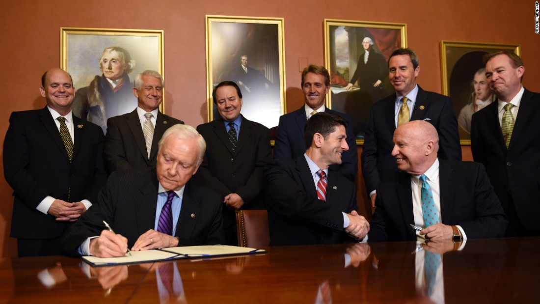 House Speaker Paul Ryan, center, shakes hands with U.S. Rep. Kevin Brady, chairman of the House Ways and Means Committee, as U.S. Sen. Orrin Hatch signs the American Manufacturing Competitiveness Act on Wednesday, May 18.