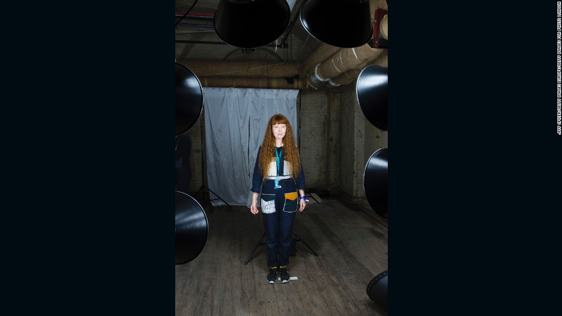 Artist Zoniel stands in front of the large bright lights of their Tintype camera. Each subject is required to stand for up to 30 seconds without moving for the image to be captured. To prepare and calm them for this intense experience, Zoniel (using her background in Buddhism) first talks them though a gentle meditation.