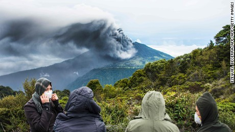 TOPSHOT - People look at the Turrialba volcano as it spewes ashes on May 20, 2016, in Cartago, Costa Rica.  The Turrialba volcano started erupting columns of smoke and ash that the wind extended towards the Costa Rican capital, in what according to experts is the strongest eruption in the past six years. / AFP PHOTO / Ezequiel BecerraEZEQUIEL BECERRA/AFP/Getty Image