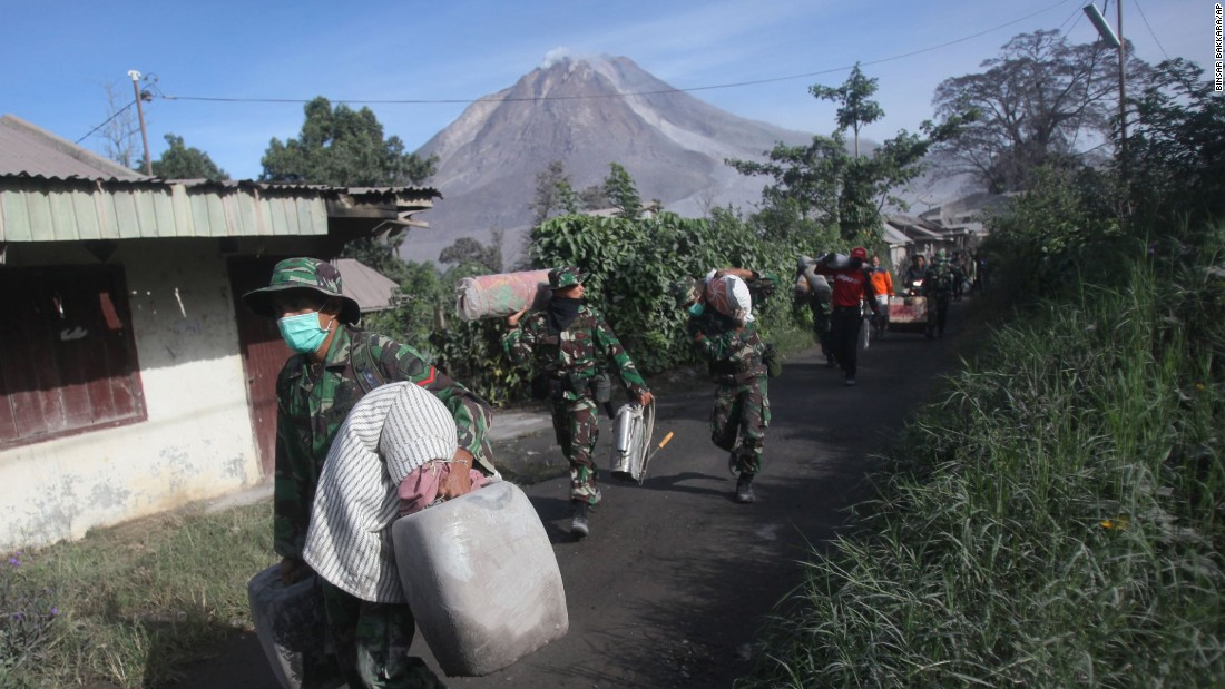 Indonesian soldiers carry people's belongings during an evacuation Sunday, May 22.