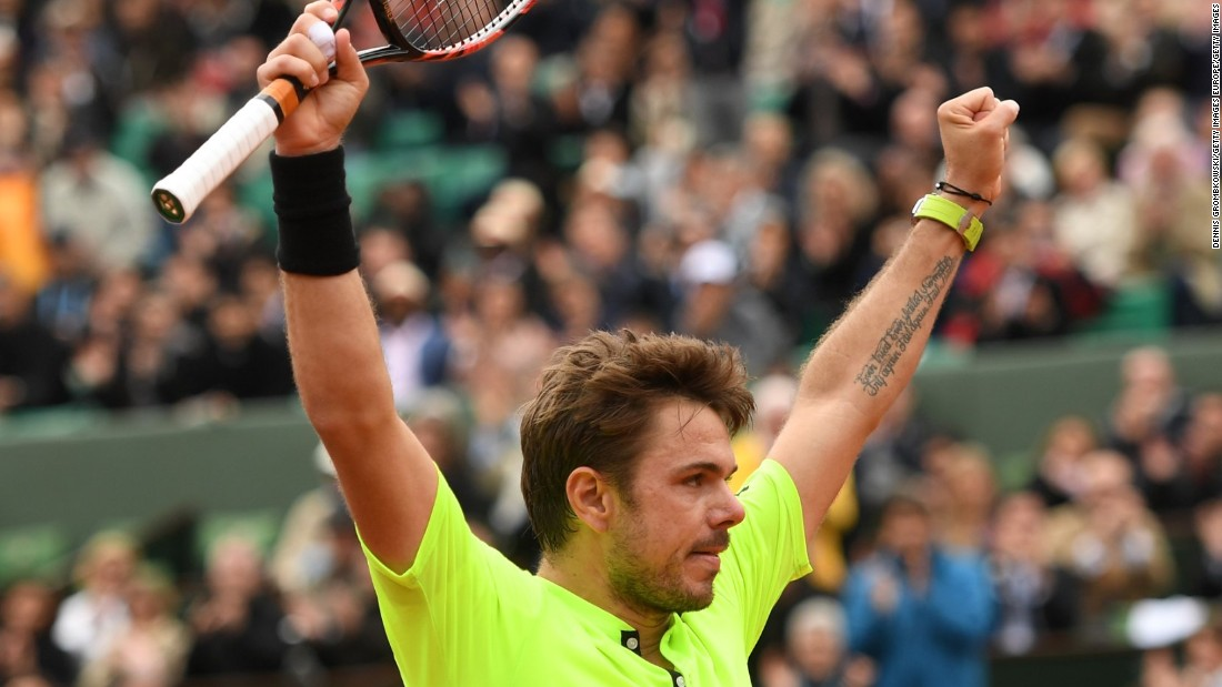Stan Wawrinka raises his arms in celebration after seeing off Lukas Rosol in five sets in the first round.