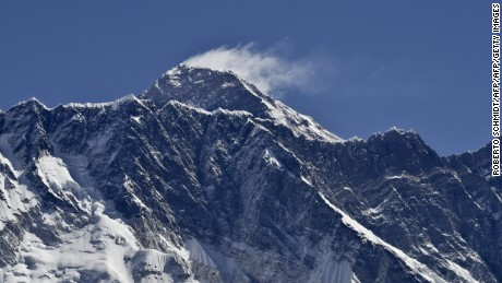 This photograph taken on April 20, 2015 shows a view of Mount Everest (C-top) towering over the Nupse, from the village of Tembuche in the Khumbu region of northeastern Nepal.  Sherpas, thought to be of Tibetan origin, have a long and proud history of mountaineering, and the term today is used for all Nepalese high-altitude porters and guides assisting climbing expeditions around Everest. The April 25 quake, which left more than 7,800 people dead across Nepal, was the Himalayan nation's deadliest disaster in over 80 years, and triggered an avalanche which killed 18 people on Everest, leading mountaineering companies to call off their spring expeditions, marking the second year with virtually no summits to the roof of the world.      AFP PHOTO / ROBERTO SCHMIDT        (Photo credit should read ROBERTO SCHMIDT/AFP/Getty Images)