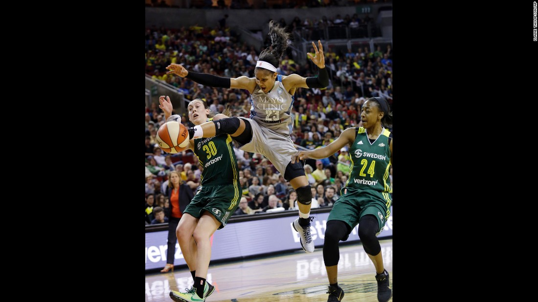 Minnesota's Maya Moore, center, loses the ball as she drives between Seattle's Breanna Stewart, left, and Jewell Loyd during a WNBA game on Sunday, May 22. All three players were No. 1 overall picks in the WNBA Draft.