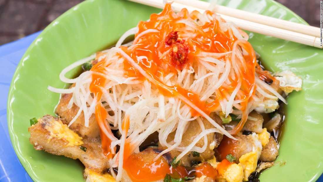 Ho Chi Minh City's favorite streetside snack. Bot chien features chunks of rice flour dough that have fried in a large wok until crispy. Then, an egg is broken into the mix. It's served with slices of papaya, shallots and green onions.