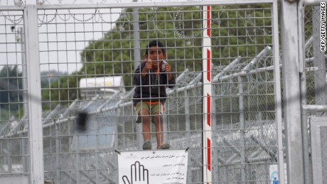A child looks through the fence at the Moria detention camp for migrants and refugees at the island of Lesbos on May 24, 2016.