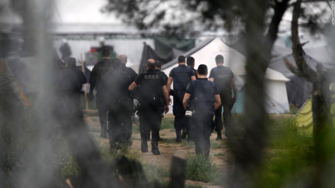 Greek policemen walk into a makeshift camp at the Greek-Macedonian border near the northern village of Idomeni on Tuesday, May 24.