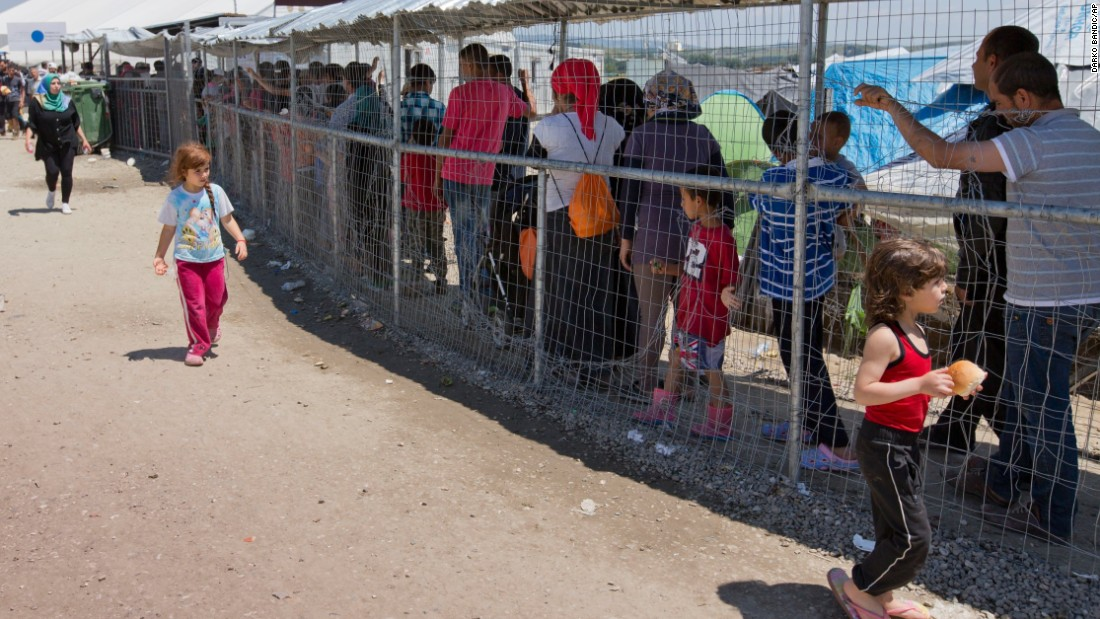 Food lines stretch along fences as people wait under makeshift shelters to receive their food quotas.
