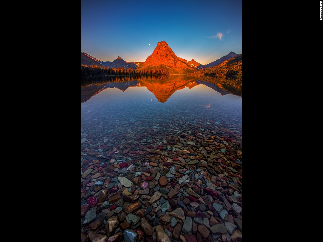 "Manish Mamtani made a pre-dawn mission to Two Medicine Lake, Glacier National Park, Montana, to capture this sunrise. ""There were no clouds but the lake water was so calm, it created a perfect reflection of the red light kissing the Sinopah Mountain,"" he says. (<a href=""http://travel.nationalgeographic.com/photographer-of-the-year-2016/"" target=""_blank"">Click here to enter NatGeo photo contest</a>)"