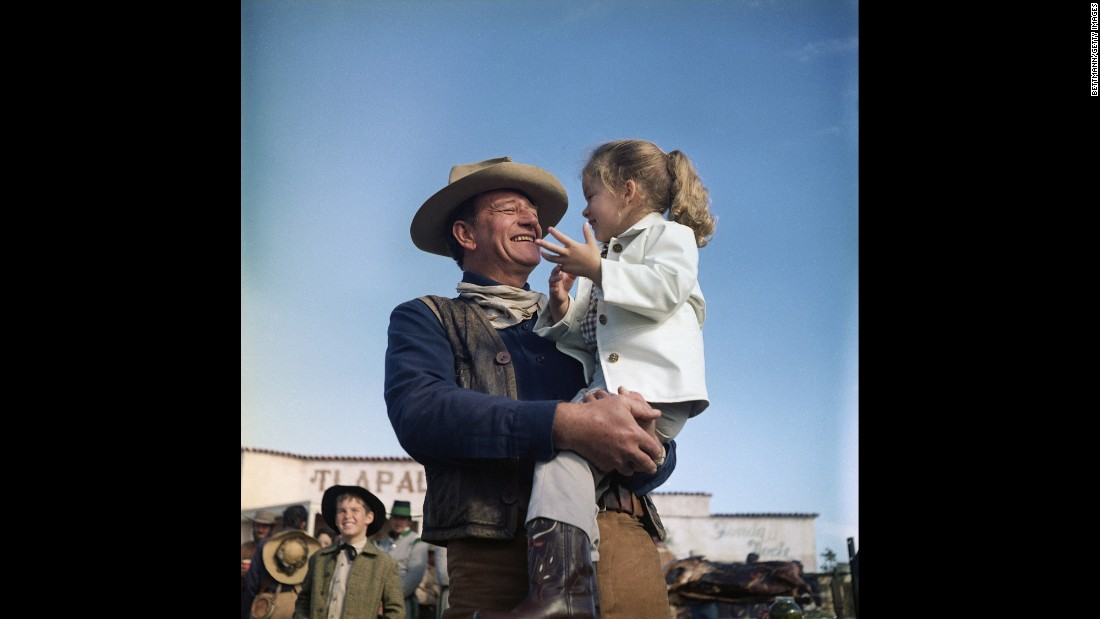 "Wayne holds his daughter Aissa on the set of ""The Alamo."""