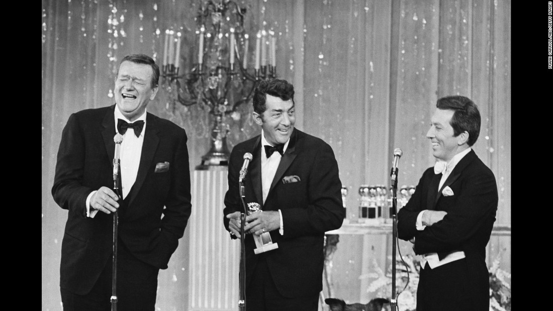 Wayne laughs on stage with singer Dean Martin, center, and host Andy Williams during the Golden Globe Awards in 1967.