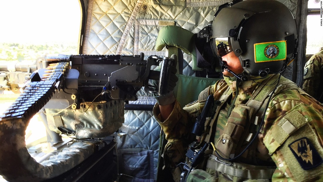 A helicopter gunner keeps watch over Taji, Iraq, as CNN flies into the next location.