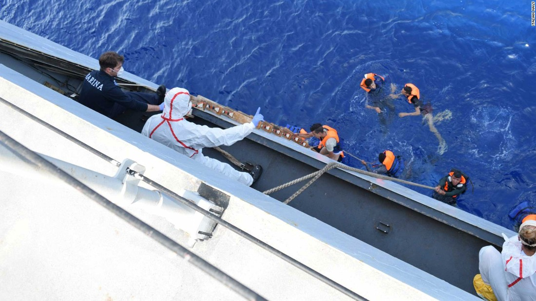 Migrants climb a ladder to the deck of the Italian navy ship.