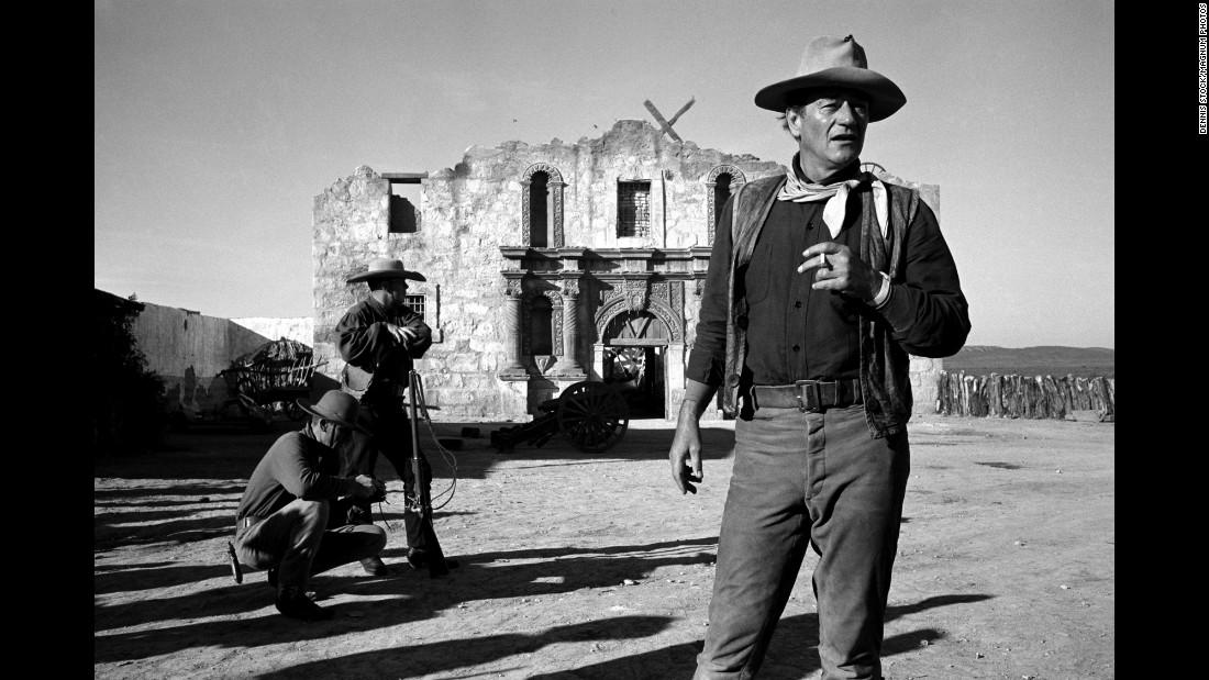 "Wayne smokes on the set of ""The Alamo"" in 1959."