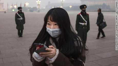 "BEIJING, CHINA - DECEMBER 09:  A Chinese woman looks at her phone as Chinese Paramilitary police wear masks to protect against pollution as they stand guard during smog in Tiananmen Square on December 9, 2015 in Beijing, China. The Beijing government issued a ""red alert"" Sunday for the first time since new standards were introduced earlier this year as the city and many parts of northern China were shrouded in heavy pollution. Levels of PM 2.5, considered the most hazardous, crossed 400 units in Beijing, lower then last week, but still nearly 20 times the acceptable standard set by the World Health Organization. The governments of more than 190 countries are meeting in Paris to set targets on reducing carbon emissions in an attempt to forge a new global agreement on climate change.  (Photo by Kevin Frayer/Getty Images)"