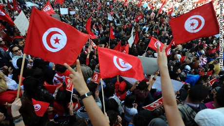 "Tunisians holding their country's flags shout during a demonstration on March 20, 2012 in Tunis.  Tunisians celebrated their country's independence day Tuesday amid fears of a widening divide between secular and religious movements in the newly democratised nation. ""This festival is an opportunity for us all to rethink our relationships, to live with our differences and despite our differences,"" President Moncef Marzouki told a flag-raising ceremony at the presidential palace in Carthage. AFP PHOTO / FETHI BELAID (Photo credit should read FETHI BELAID/AFP/Getty Images)"